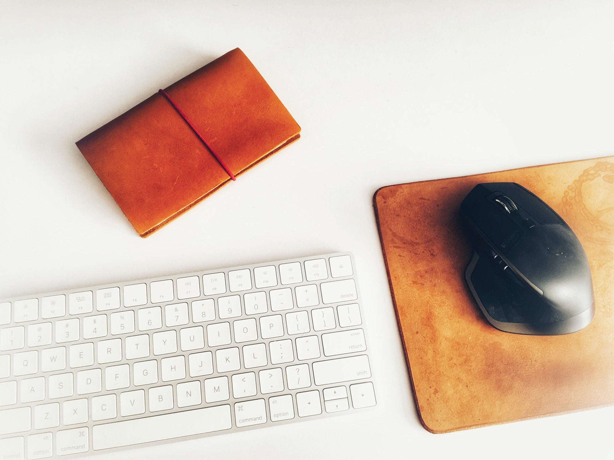 keyboard, leather mouse pad, and mouse on a white surface
