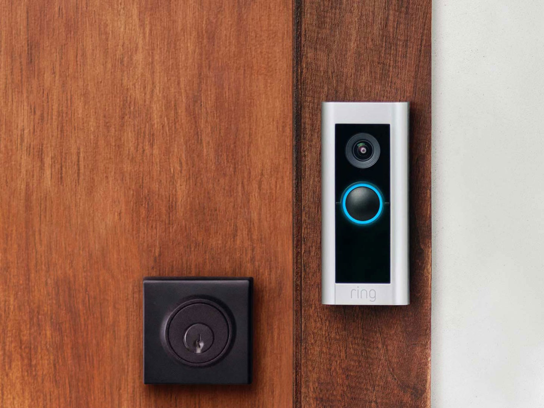 Ring Video Doorbell Pro 2 installed on a brown wooden door near a deadbolt lock.