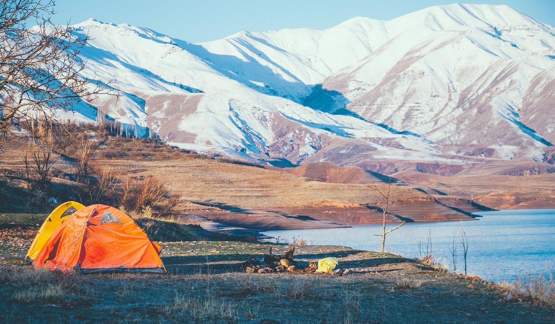 orange tent on grass near a green, snowy mountain