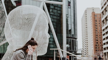 Person with long brown hour talking on iPhone in front of statue