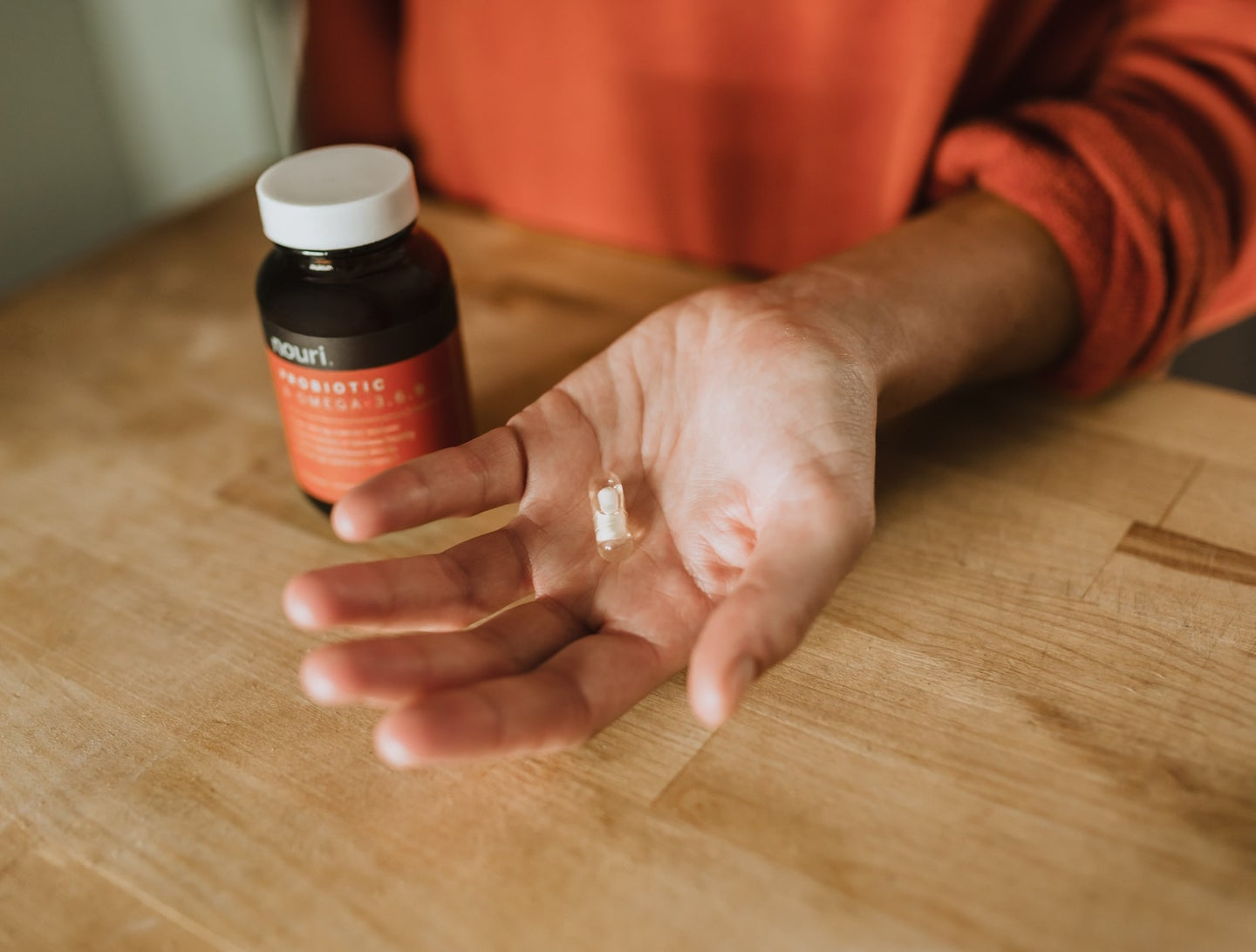Person in an orange shift holding a white probiotic pull next to a brown vitamin bottle