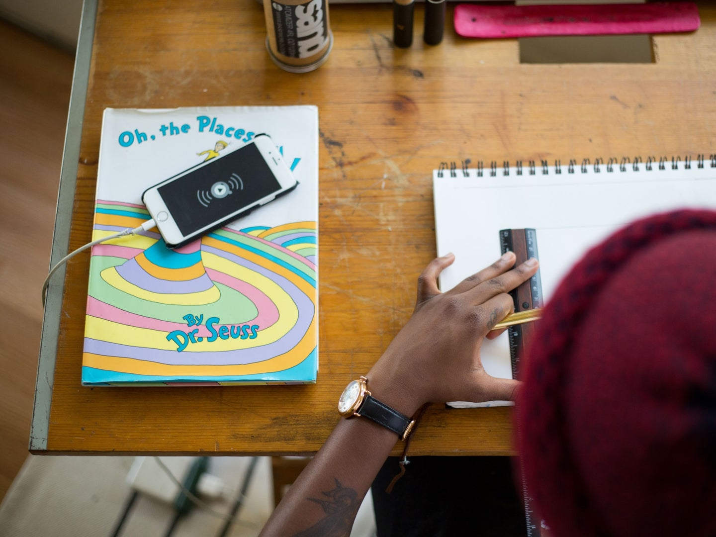 A person sitting at a desk, drawing, with their phone battery charging on a cable next to them.