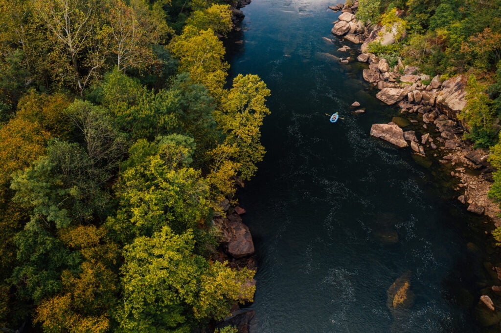 A drone shot of a raft on the New River Gorge National Park and Preserve.