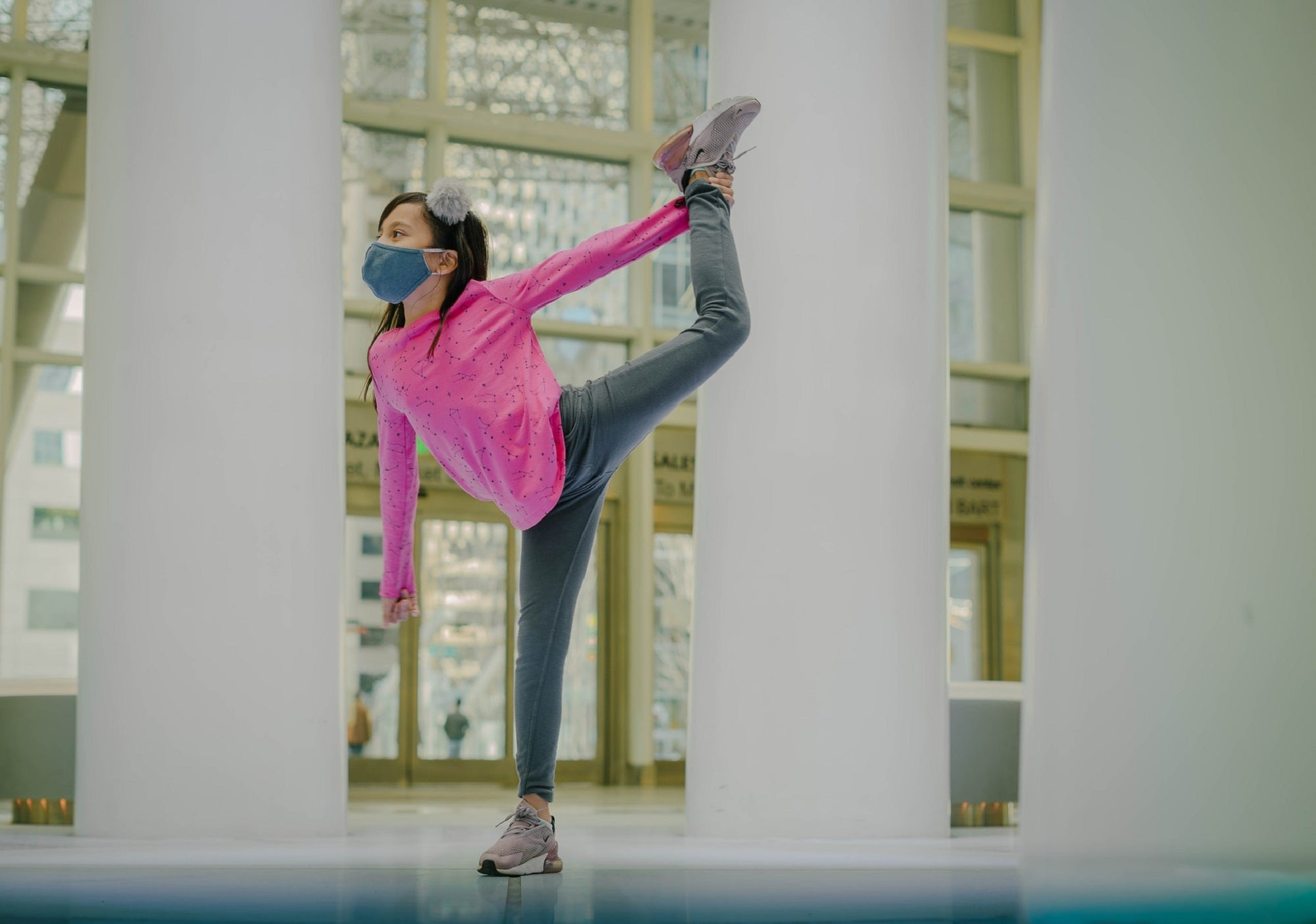 Child in a pink shirt and hair bow wearing a mask and holding a dance pose inside an atrium
