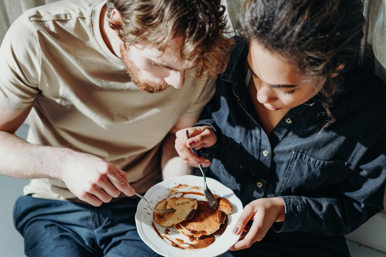 a man and woman sit close to each other and share a plate of pancakes