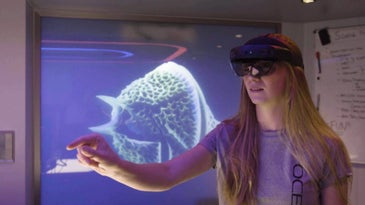 A woman wearing a Microsoft Hololens and interacting with an invisible hologram that only she can see.
