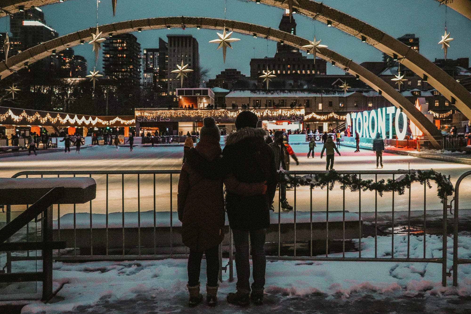 two people hugging each other in front of a lit up ice skating rink