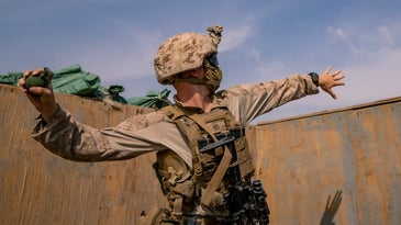 A US Marine in desert camo about to throw a grenade out of a bunker.