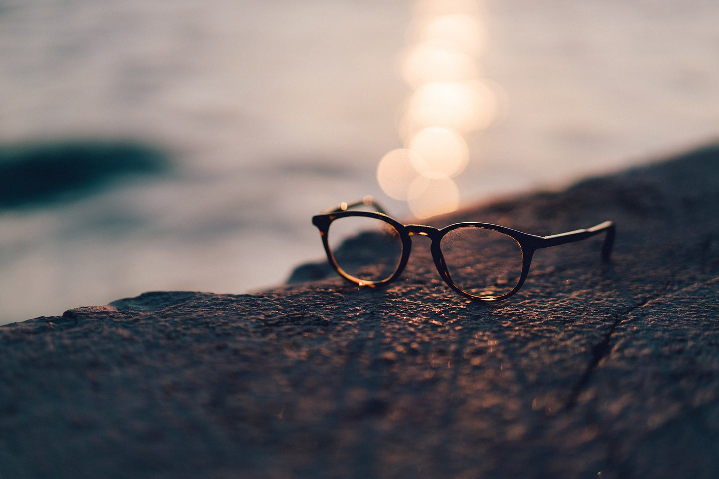 glasses near water with the sun casting a shadow