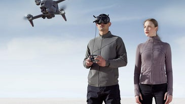Two people flying a DJI FPV drone in a non-descript setting with a blue sky.