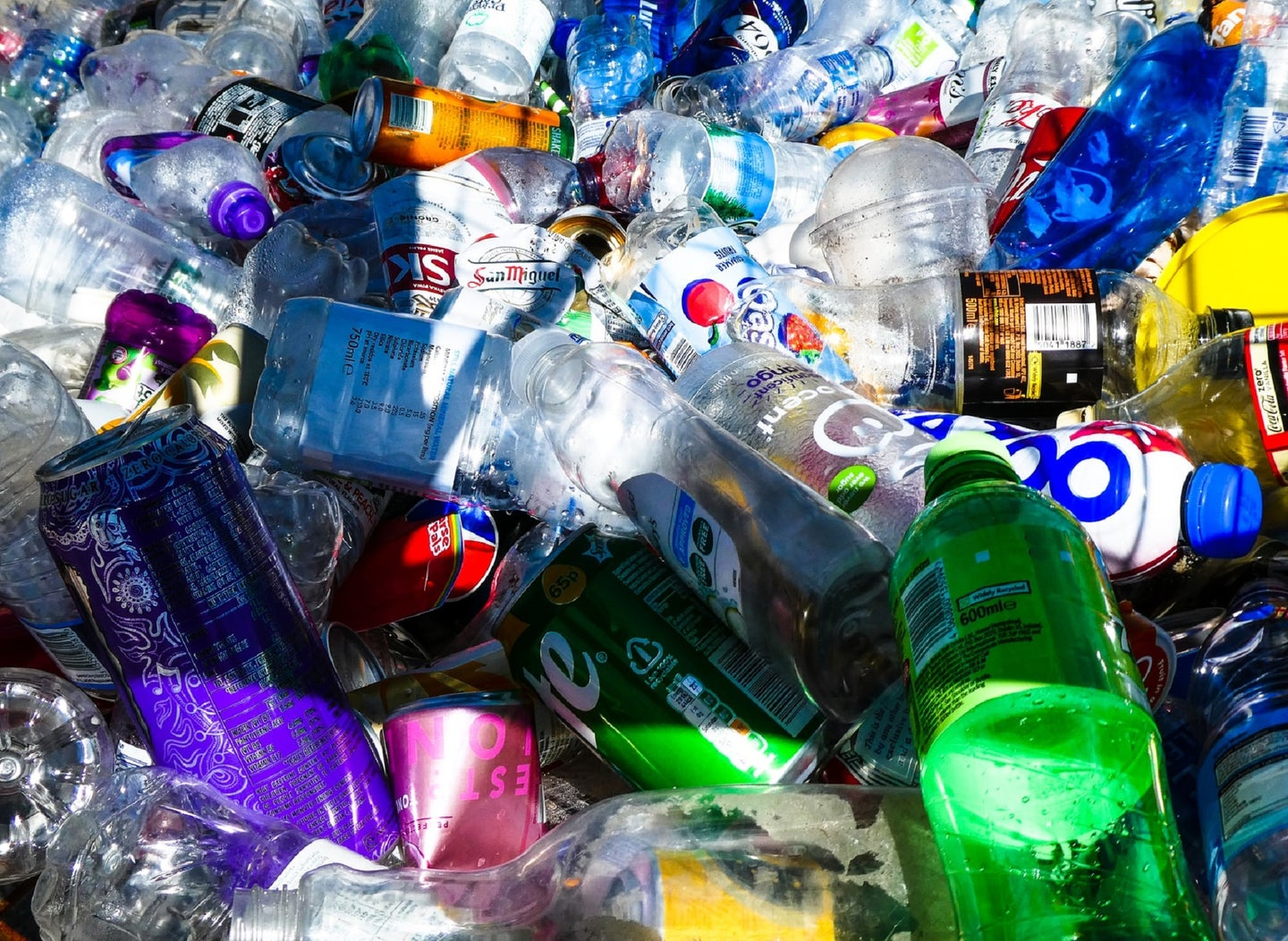 Plastic water bottles and aluminum soda cans in a bin