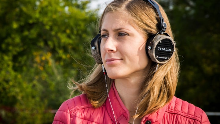 A woman in a pink jacket outside near some trees, listening to music on a pair of Thalia headphones.