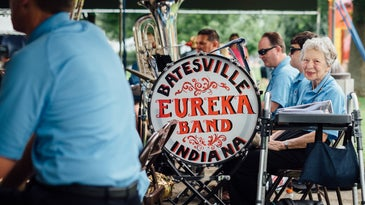 Elderly person in a blue uniform sitting next to a marching band drum that says Batesville Eureka Band Indiana