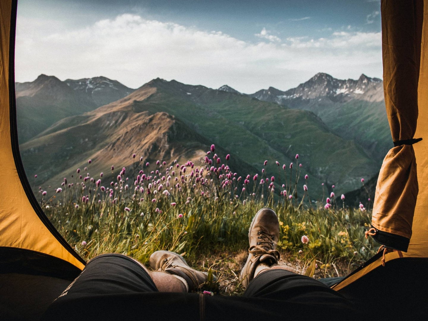 Person camping in the outdoors with feet out of tent.