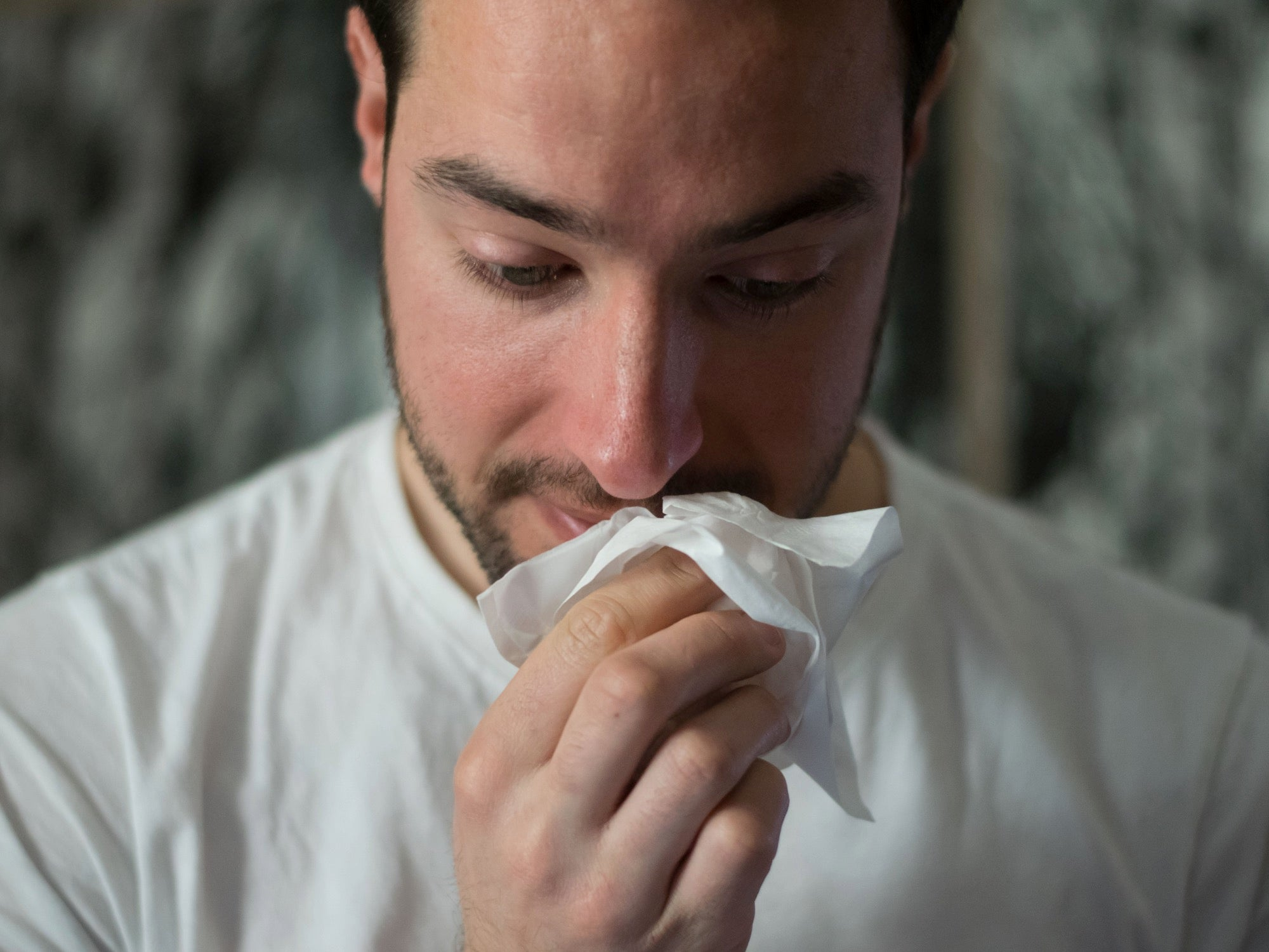 man wiping his nose with a tissue