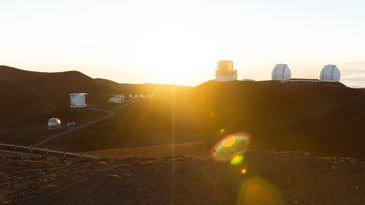 The sun over Maunakea volcano and research observatories in Hawaii