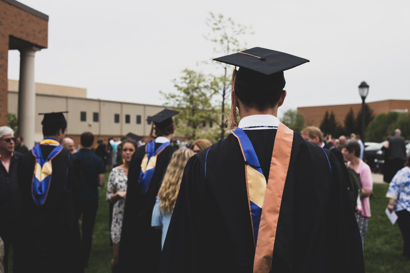 people at a graduation ceremony wearing caps and gowns outside
