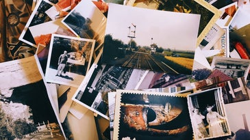 Old printed photos scattered around a table.