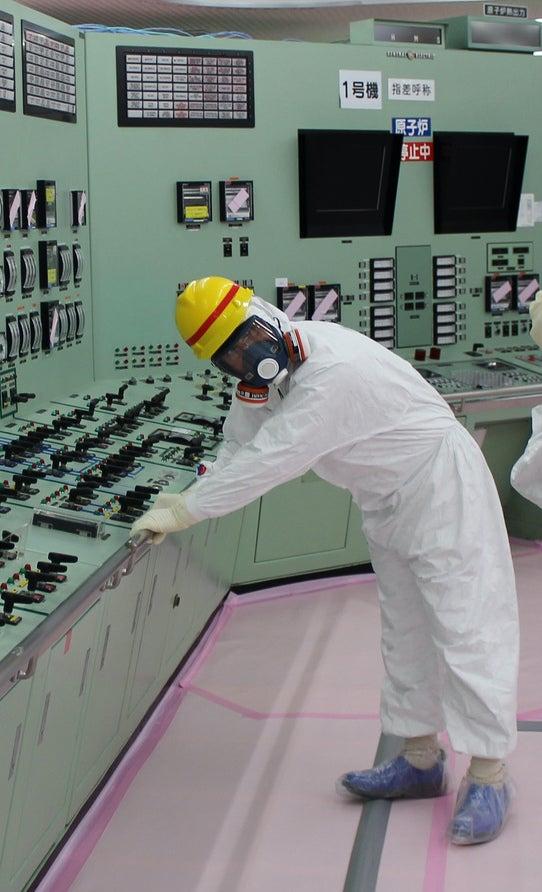 Scientist holding an earthquake railing in a Fukushima Daiichi control room