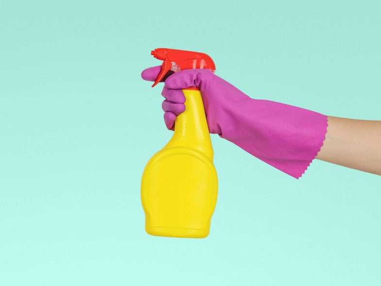 Hand in rubber gloves with a cleaning product sprayer