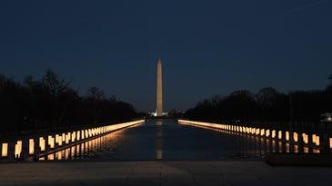 Washington Memorial at night with rows of lights along a pool
