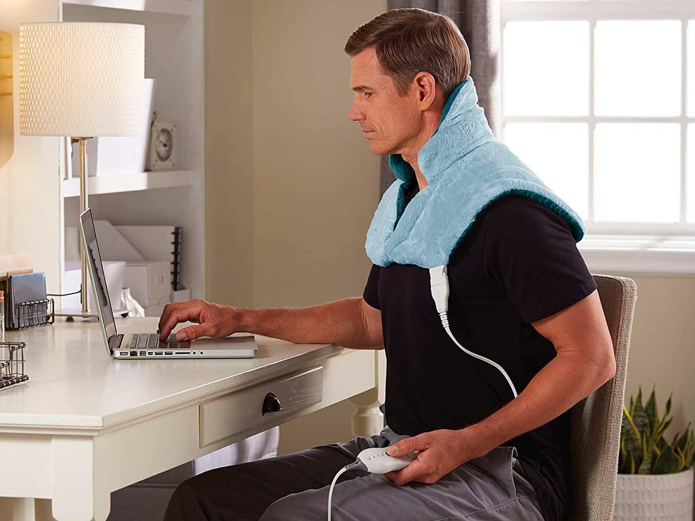 Man wearing neck heating pad