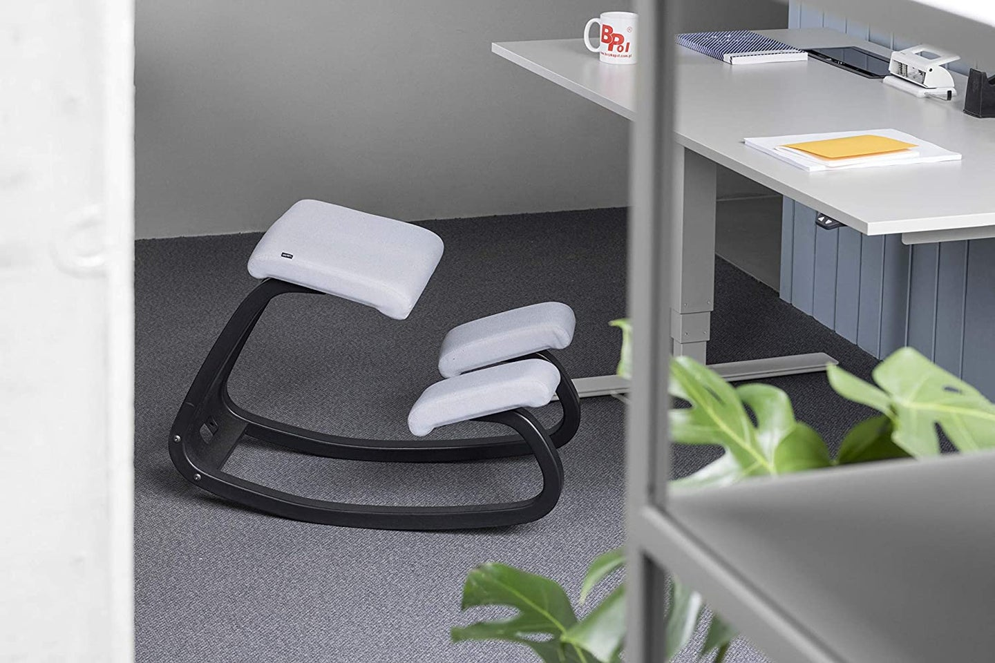 black and grey kneeling chair next to a silver desk