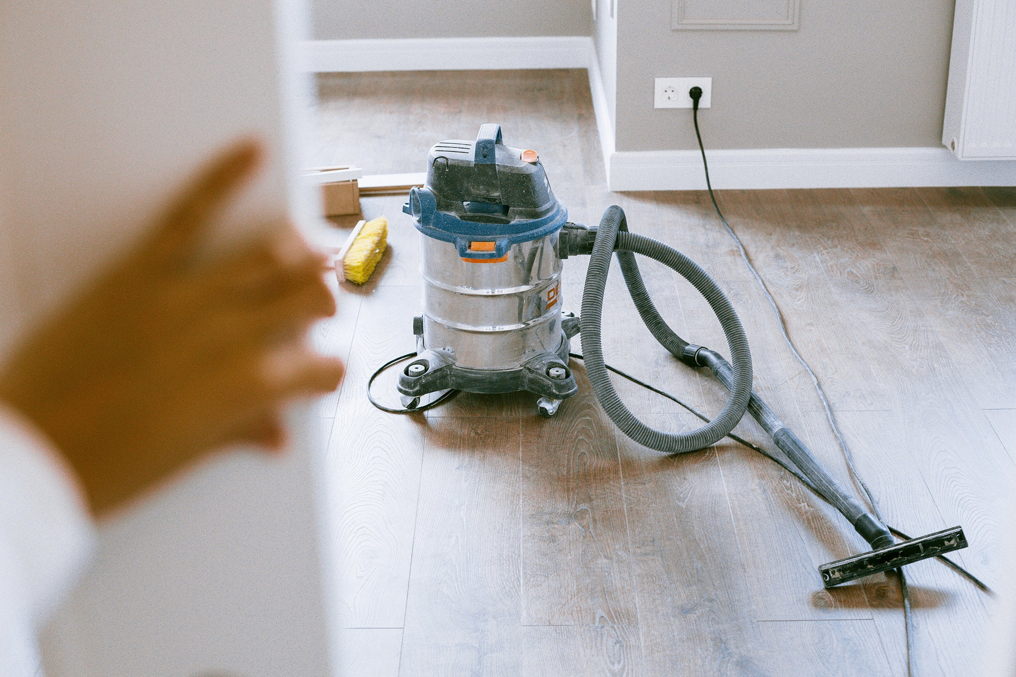 the best shop vac on the floor and a hand holding a door