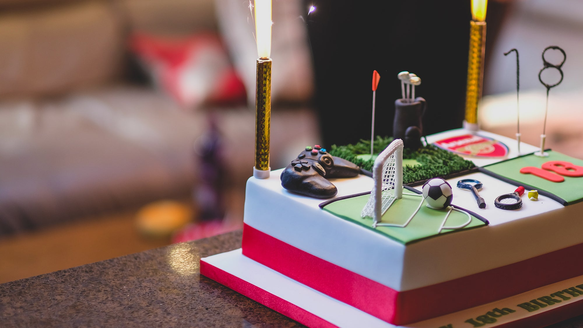rectangular 18th birthday cake with sparklers and games on it