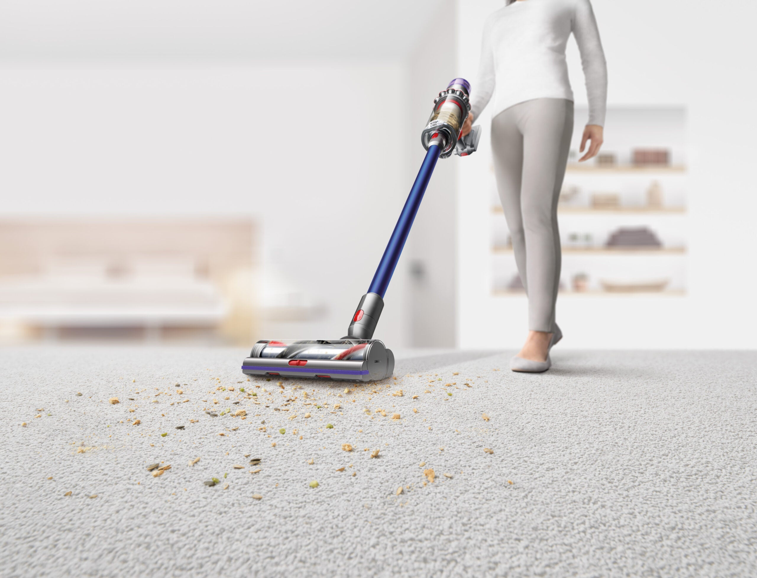 Person using the best dyson vacuum to clean up crumbs on a white rug