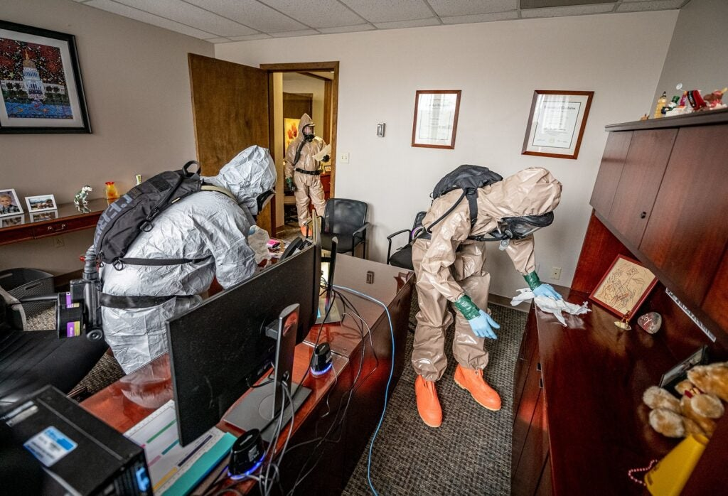 Haz-mat experts in suits and PPE sanitize desks in an office