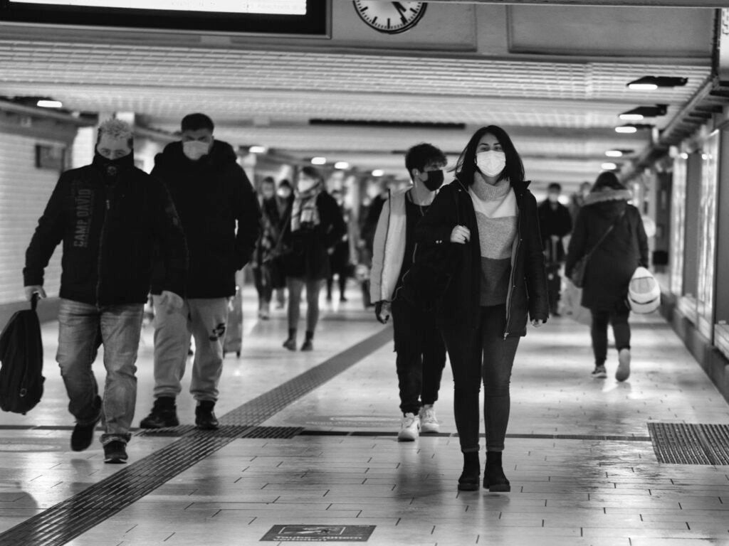 people walking in a train station with masks on
