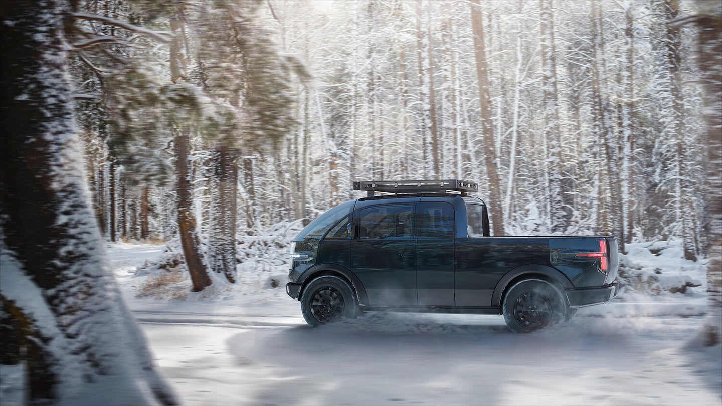 Canoo electric pickup truck driving through snow with a roof rack