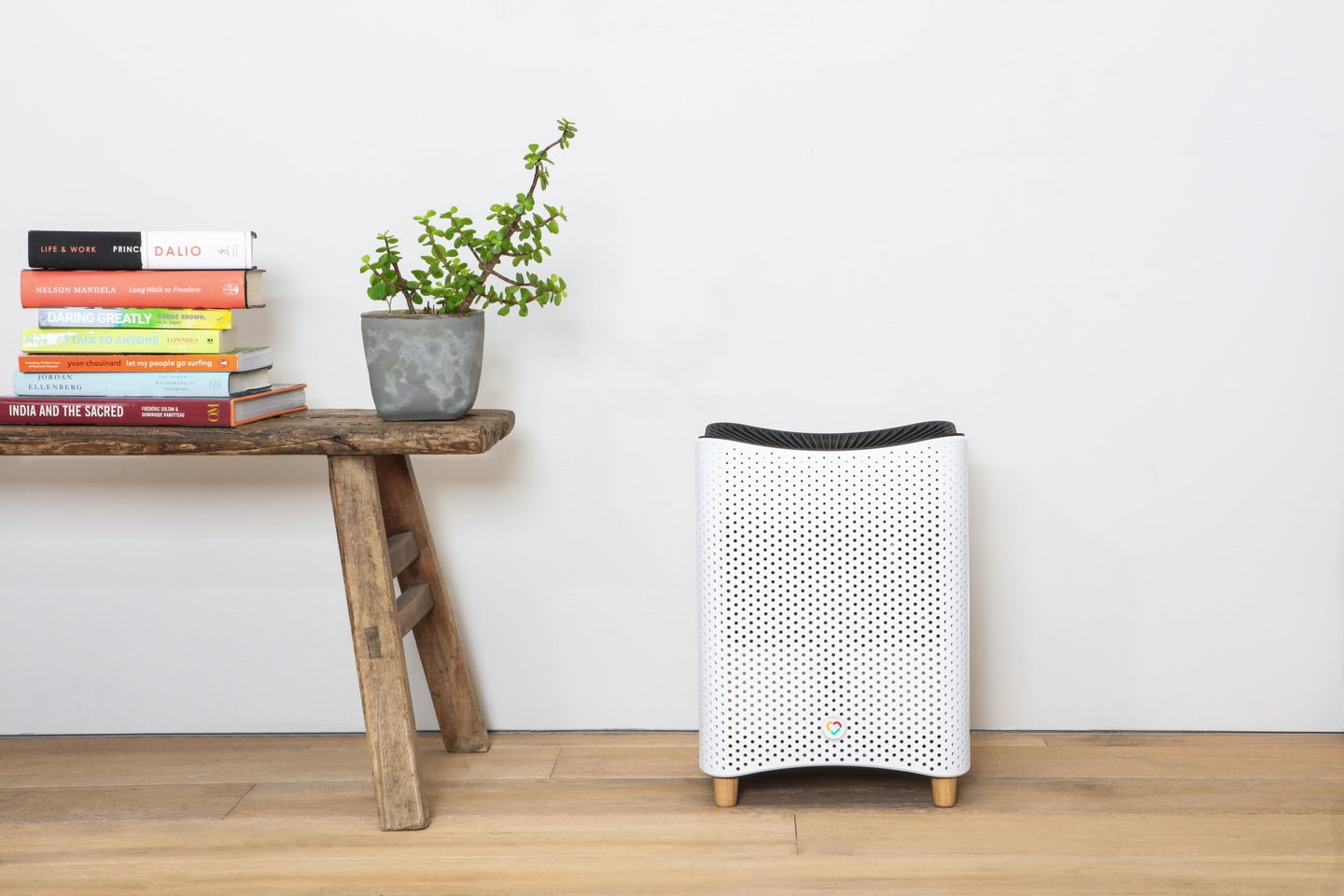 Mila air purifier, one of the best air purifiers, on a wood floor next to a wooden bench with a plant and books on it