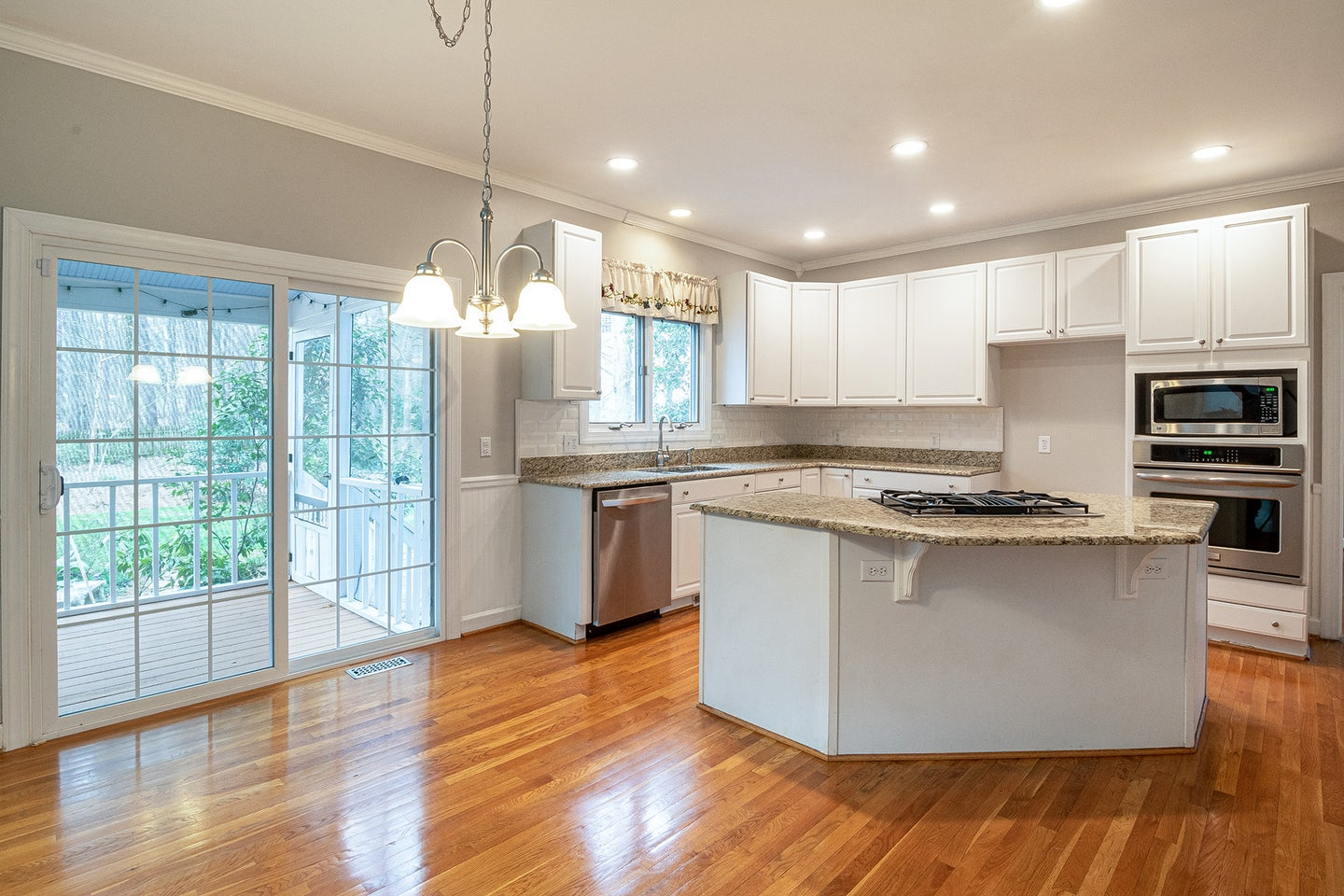 a clean kitchen with shiny wood floors and white cabinets