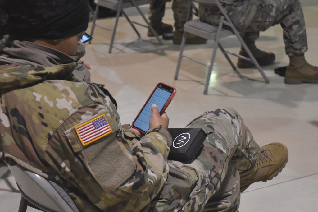 A soldier holds a smartphone.