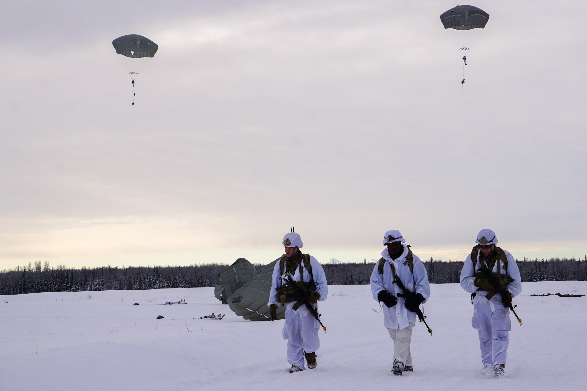 Three paratroopers walk across a snowy field.