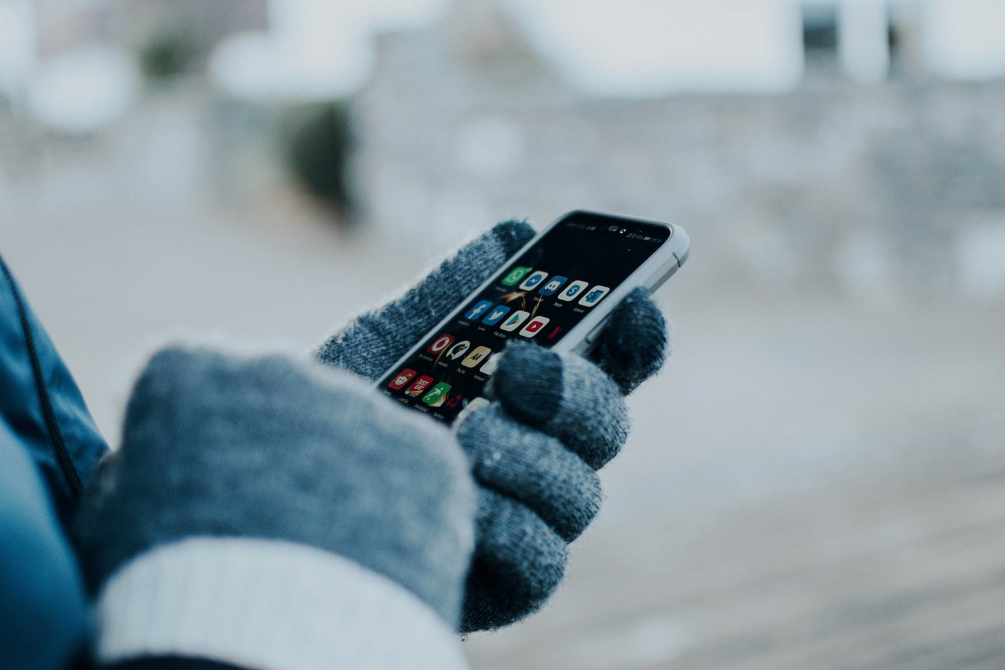 Person wearing gloves using an iPhone
