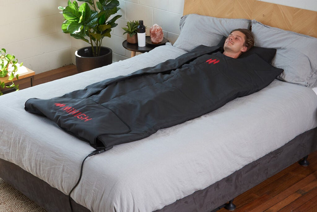 guy in a bed in a heated sauna blanket