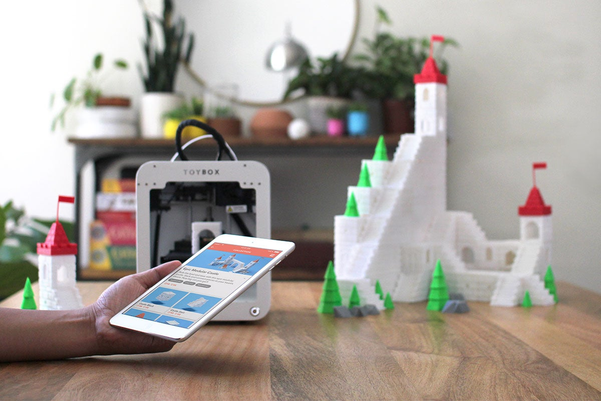 person with a 3d printer, tablet, and a 3d-printed castle