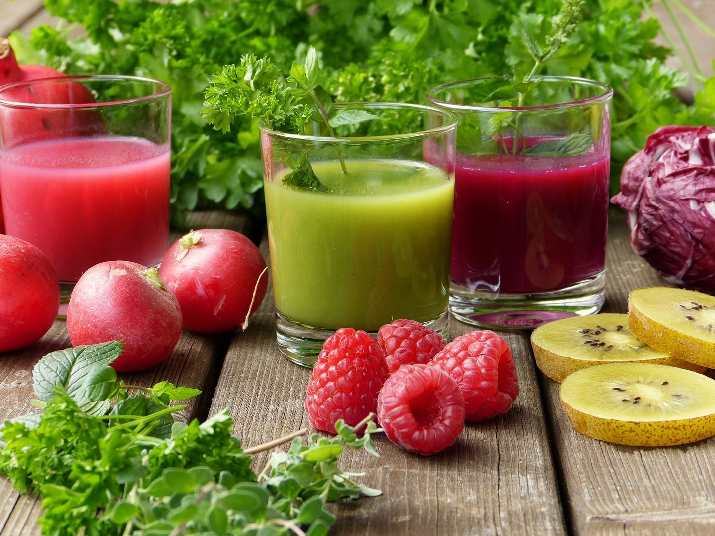 Glasses of juice, smoothies, and berries on a table.
