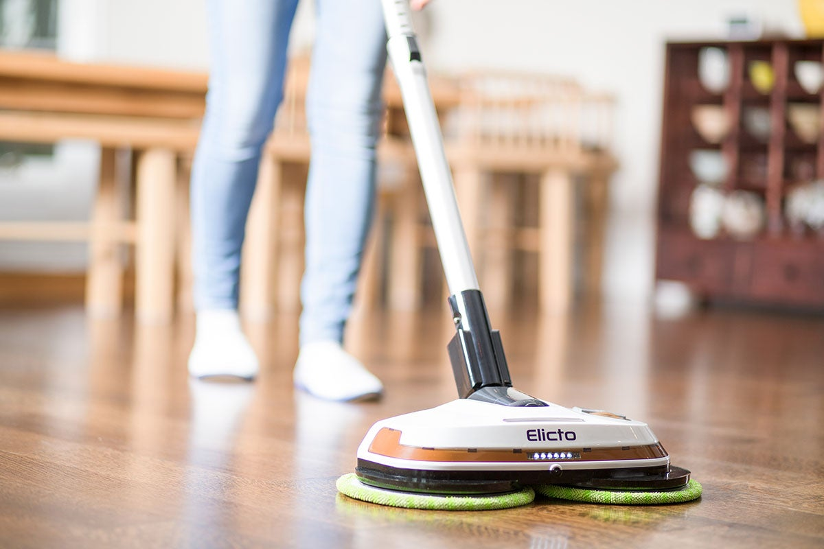 person using a floor cleaner on a wooden floor
