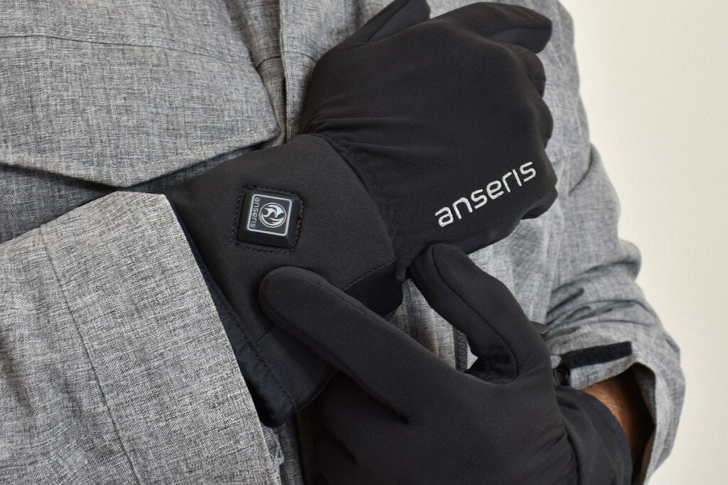 person in a grey jacket with black heated glove liners on