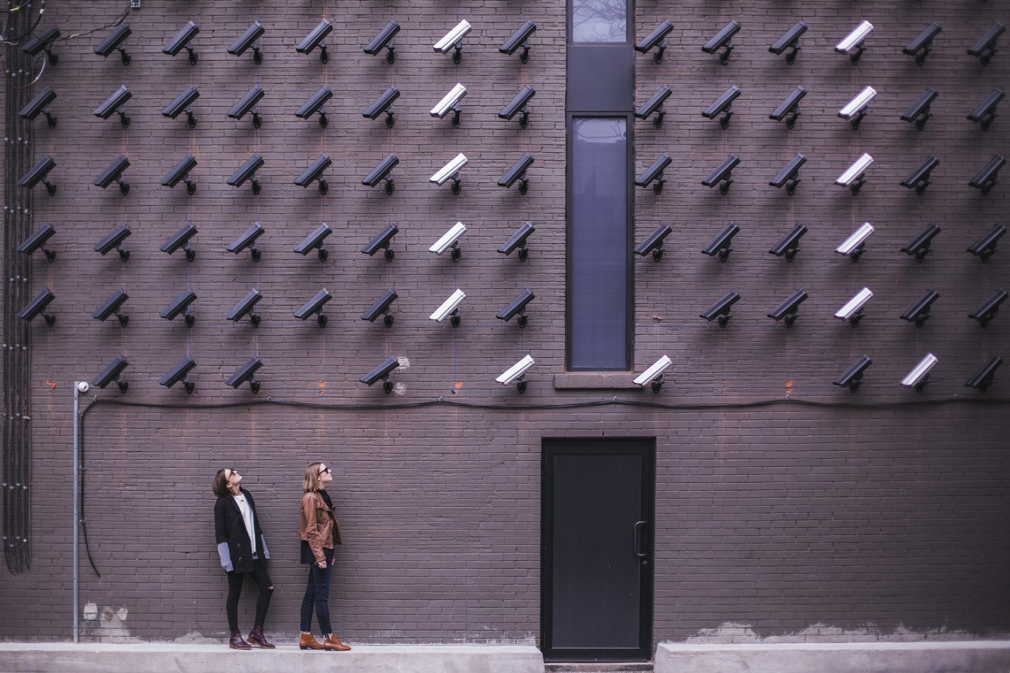 two people looking up at a lot of black and white security cameras mounted on a wall