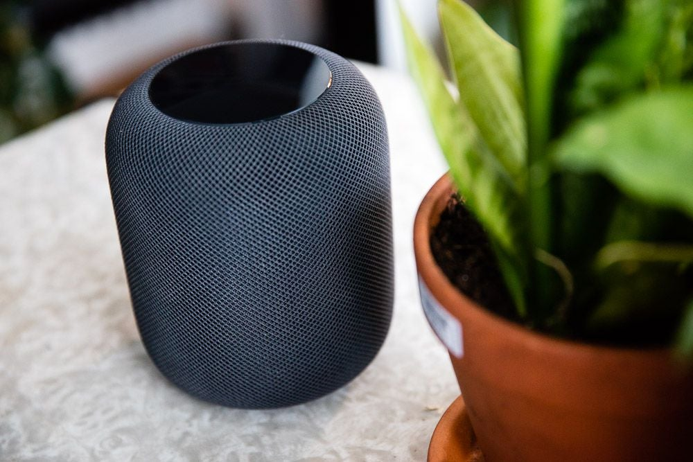 Apple's original HomePod smart speaker next to a plant on a table.