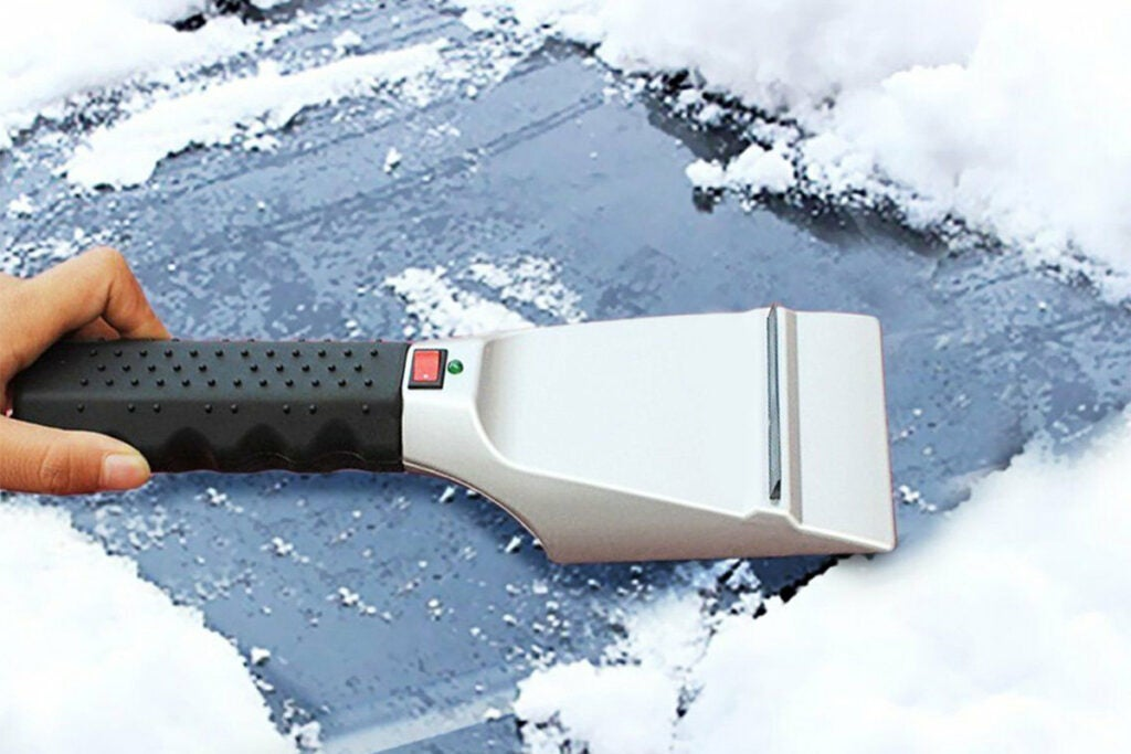 person holding a heated ice scraper over a snowy window-shield