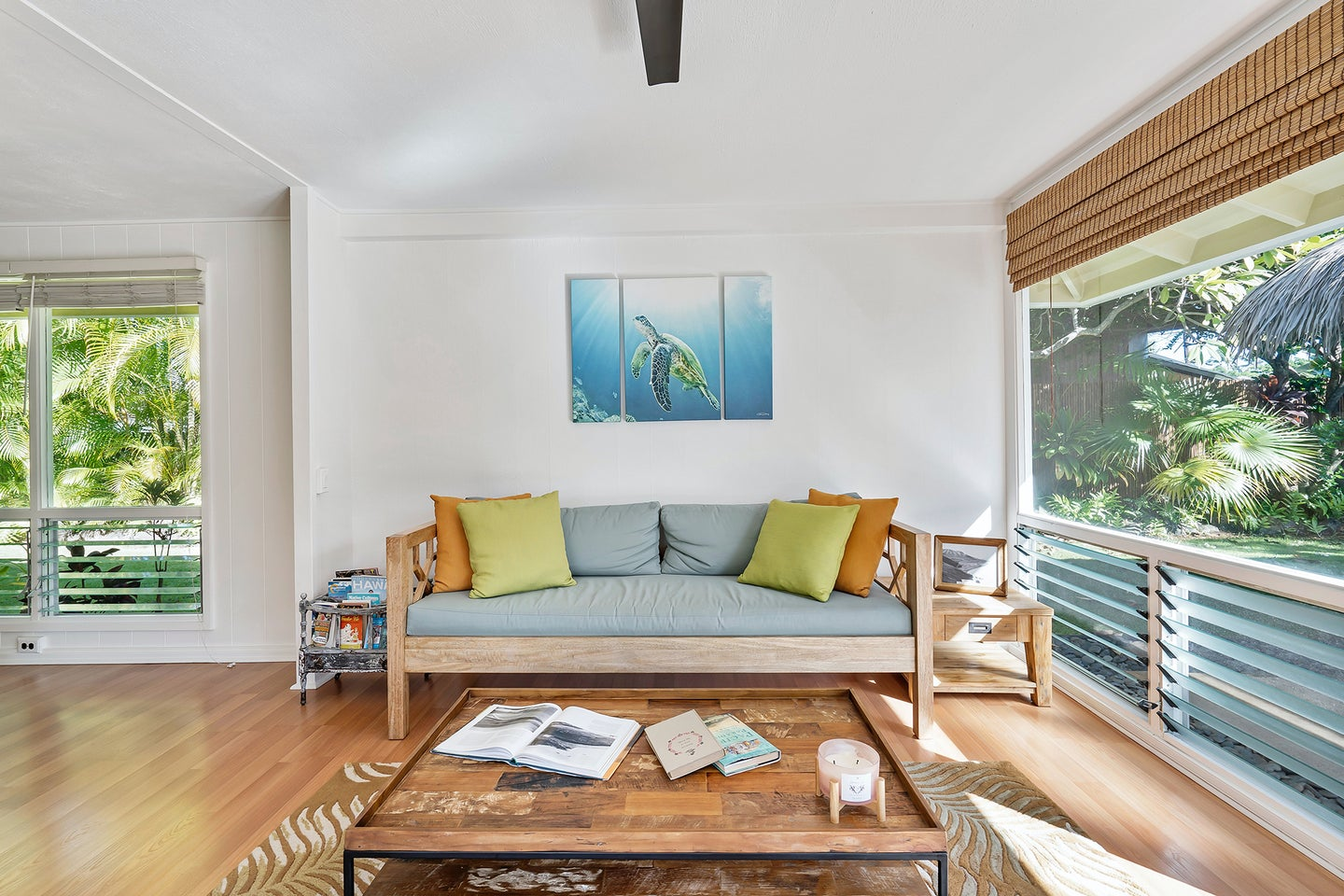 Living room with a couch, wooden coffee table, and a turtle painting on the wall