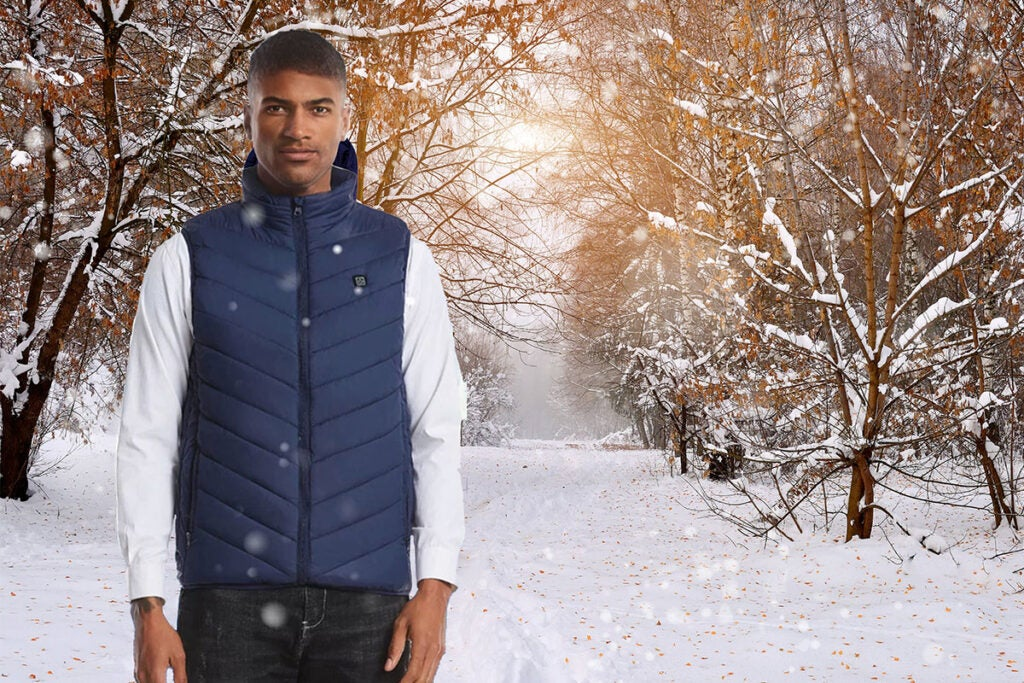 man in a blue vest in front of a snowy forest