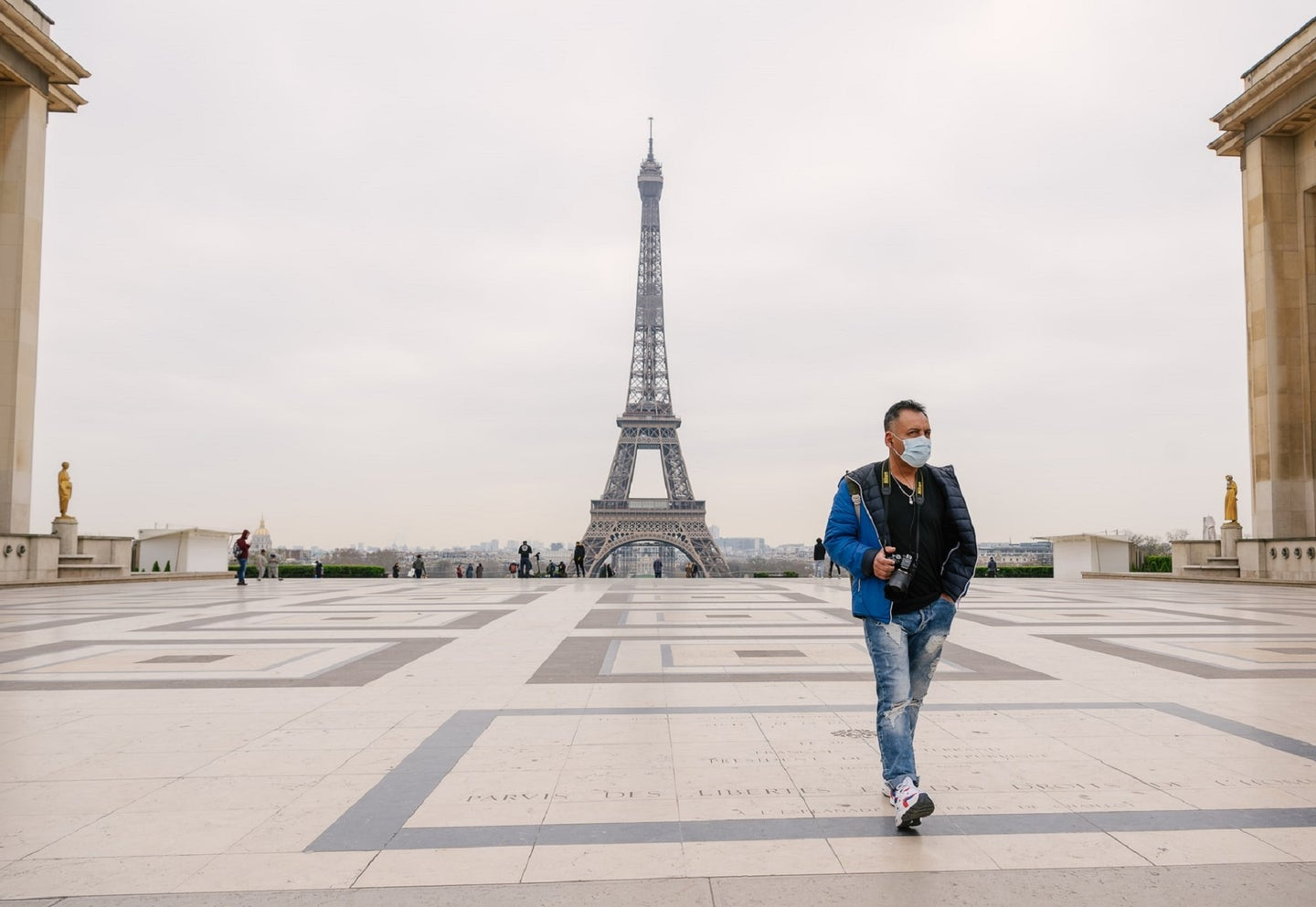 Tourist in surgical mask in front of the Eiffel Tower