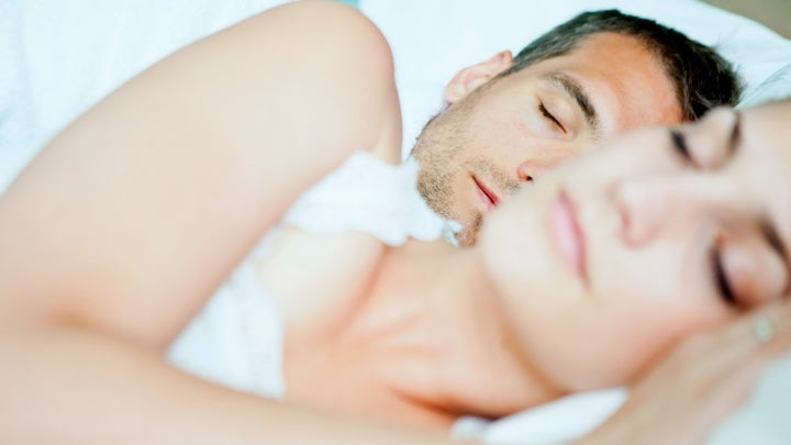 a man and a woman lay sleeping in bed